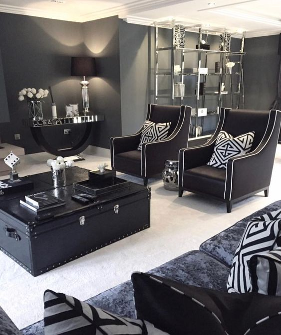 a stylish living room done in mostly black and graphite grey with touches of white to refresh the space and vintage furniture