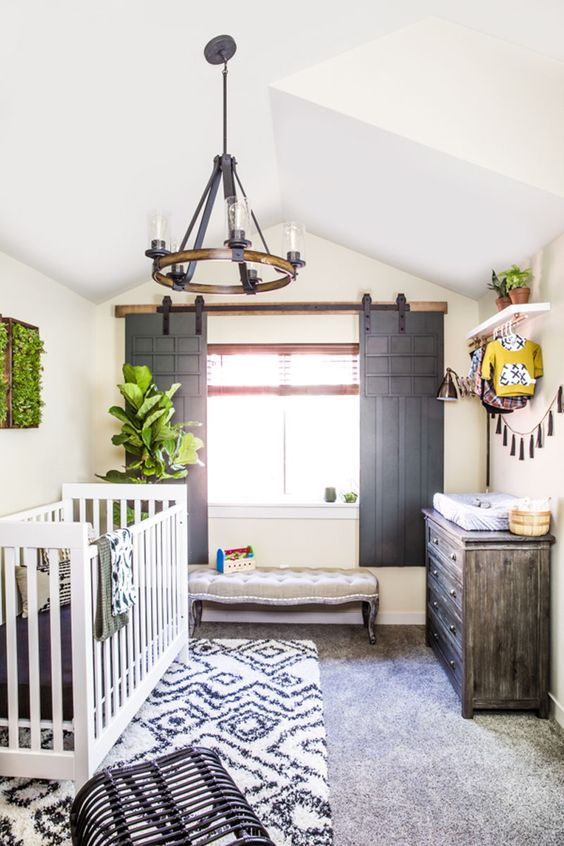 a unique farmhouse nursery with sliding shutters of vintage doors, a white crub, printed layered rugs and a vintage chandelier