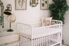 a vintage farmhouse nursery with a white crib, a shabby chic dresser, a printed rug and greenery