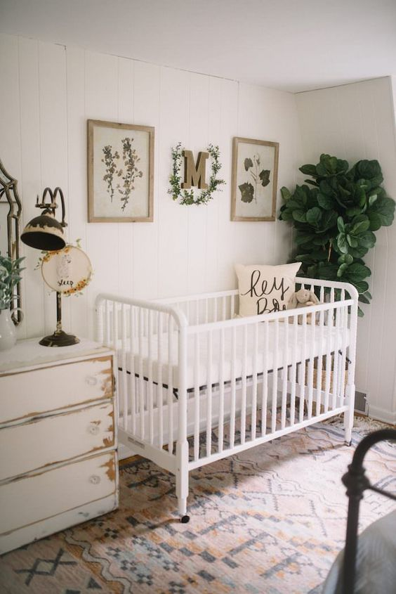 a vintage farmhouse nursery with a white crib, a shabby chic dresser, a printed rug and greenery