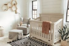 a vintage farmhouse nursery with a white shiplap wall, a printed rug, a grey vintage crib and a hanging planter