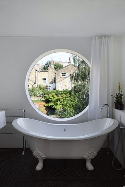 a vintage-inspired neutral bathroom with a dark floor and a large porthole window that can be covered with a curtain