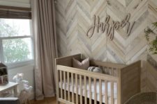 a warm neutral farmhouse nursery with a reclaimed wooden wall with a herringbone pattern, a bead chandelier, a cool rug and a stained crib