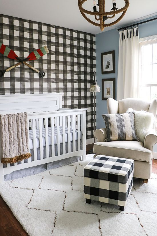 a welcoming farmhouse nursery with a plaid statement wall and a matching ottoman, neutral furniture and a unique sphere chandelier