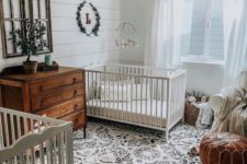 a welcoming shared farmhouse nursery with a printed rug, a leather ottoman, a stained dresser, a bead chandelier and some greenery