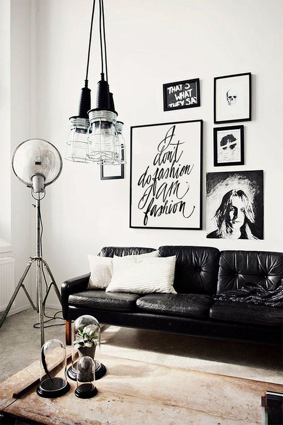 an edgy living room with a gorgeous gallery wall, a black leather sofa, a cluster of pendant lamps and a wooden coffee table