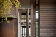 02 Its exterior done with dark wood and aged metal blends the landscape, while lots of windows bring much light and views in