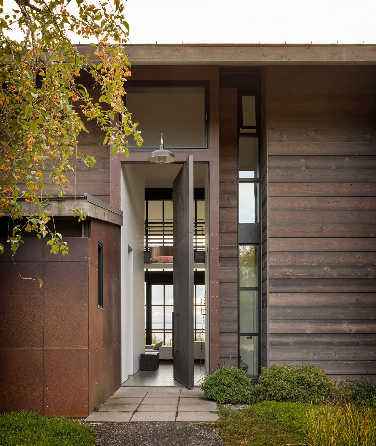 Its exterior done with dark wood and aged metal blends the landscape, while lots of windows bring much light and views in