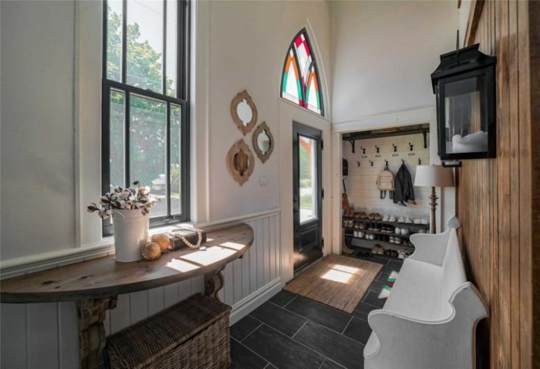 The entryway is done with much natural wood, dark tiles, and white wood cladding all the walls