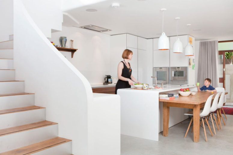 The kitchen is done with sleek white cabinets, catchy pendant lamps and some wooden furniture