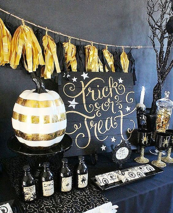 a black and gold dessert table with black and gold tassel garland, a striped pumpkin, glitter and some spider glasses