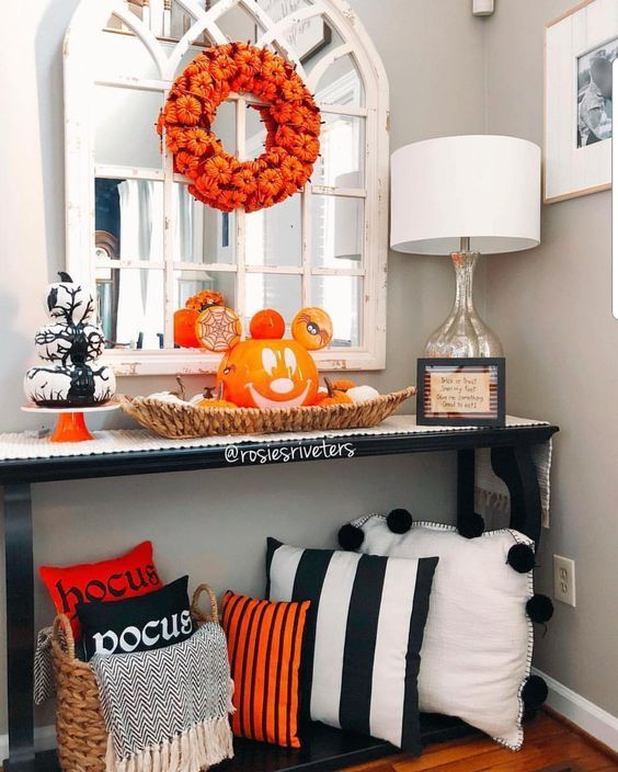 a bright Halloween entryway console with black, white and orange pillows, a Jack-o-lantern, a pumpkin wreath and a stack of white pumpkins