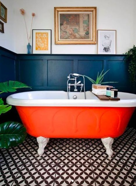 a bright orange bathtub with claw feet is a cool fall-inspired idea for a bathroom and will raise the spirits