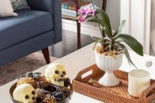 02 a chic Halloween coffee table with a potted bloom, a bowl with spiders, skulls and pinecones and some bones in a shell