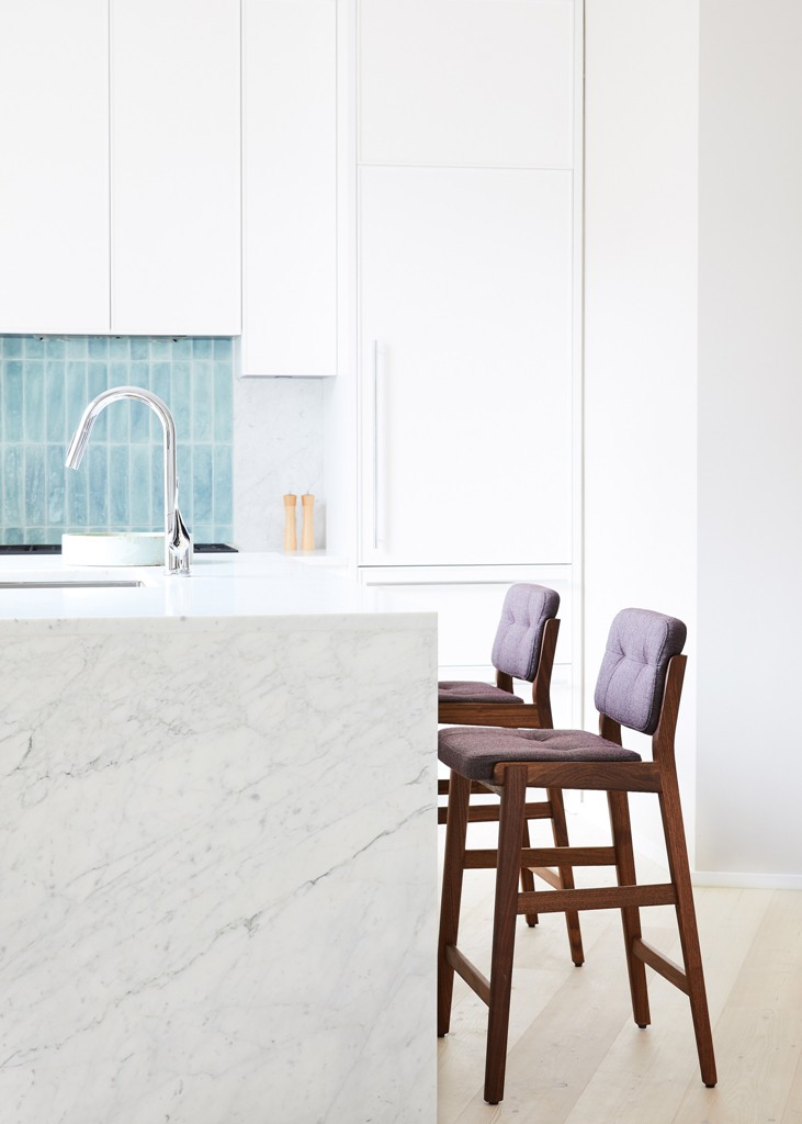 The kitchen is done with white cabinets, a white marble kitchen island and tall stools that contrast the whole space