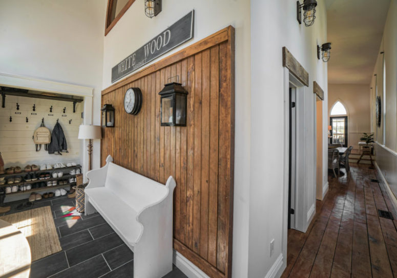 The wooden bench, built-in shelves and a stained wood wall make the entryway super cozy and functional