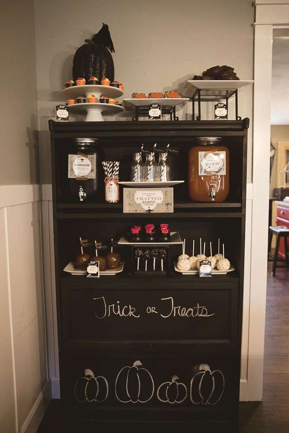 a black dessert table with chalking, blackbirds, a sparkling black pumpkin and lots of food and drinks