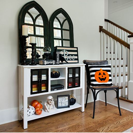 a bright Halloween entryway with skeletons, pumpkins, signs and a pumpkin pillow is easy to realize