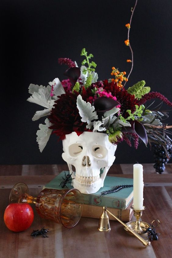 a chic centerpiece of a skull and dark and moody florals, pale and usual greenery and some berries look very cool