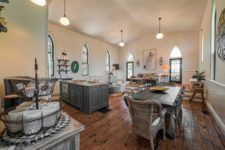 04 The kitchen and dining space are united, with stained and grey wooden furniture and comfy rattan chairs – a wonderful space to have a meal