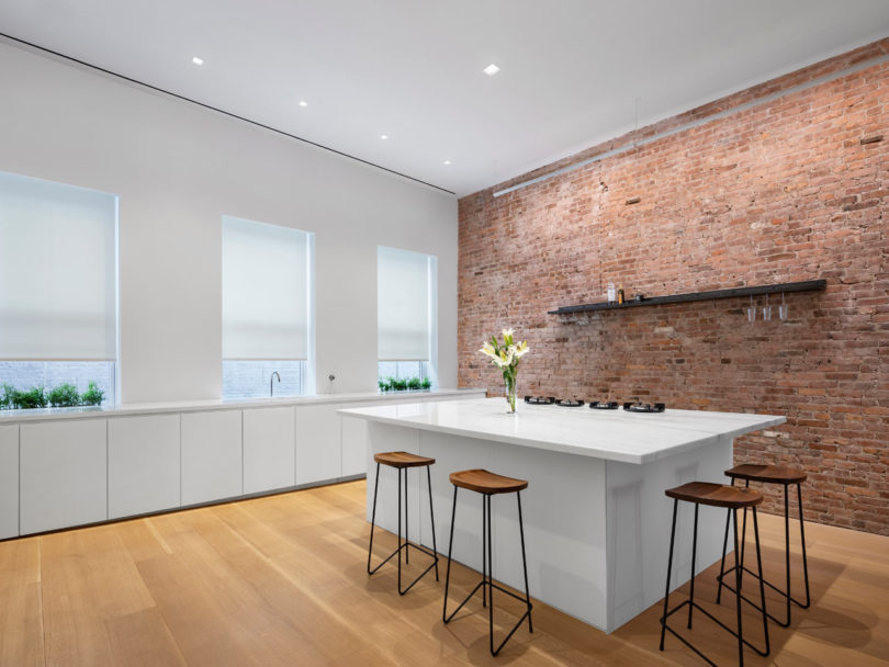 The kitchen is white and long, there are no upper cabinets and a white kitchen island with stools for eating