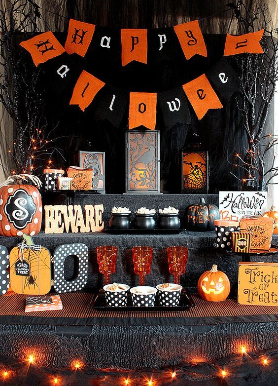 a bold food station for Halloween decorated with lights, bunting, letters, signs and colored glasses and cauldrons