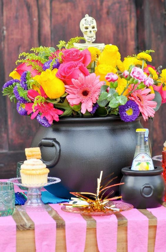 a bright Halloween centerpiece of a black cauldro, bright blooms in pink, purple and yellow plus a skeleton
