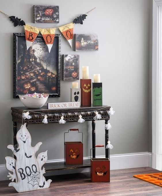 a chic Halloween entryway with a whimsy gallery wall, tassel garlands, ghosts, Jack-o-lanterns, a fabric bunting