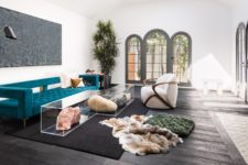 05 The living room is done with catchy and sculptural modern furniture plus acrylic tables with rocks inside