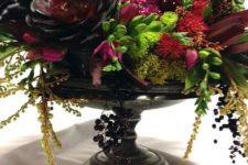 05 a black bowl with succulents, cascading greenery and branches, dark blooms and a sprakling red skull