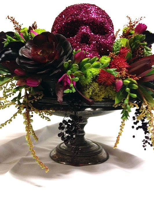 a black bowl with succulents, cascading greenery and branches, dark blooms and a sprakling red skull