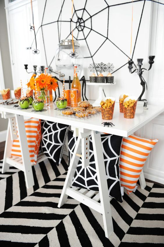 a bold Halloween buffet in black, white, orange and green, with spiderwebs and bright blooms
