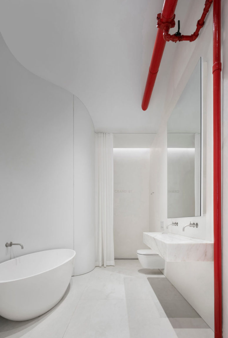 The bathroom is white and minimalist, with touches of red, an oval tub and a marble floating vanity