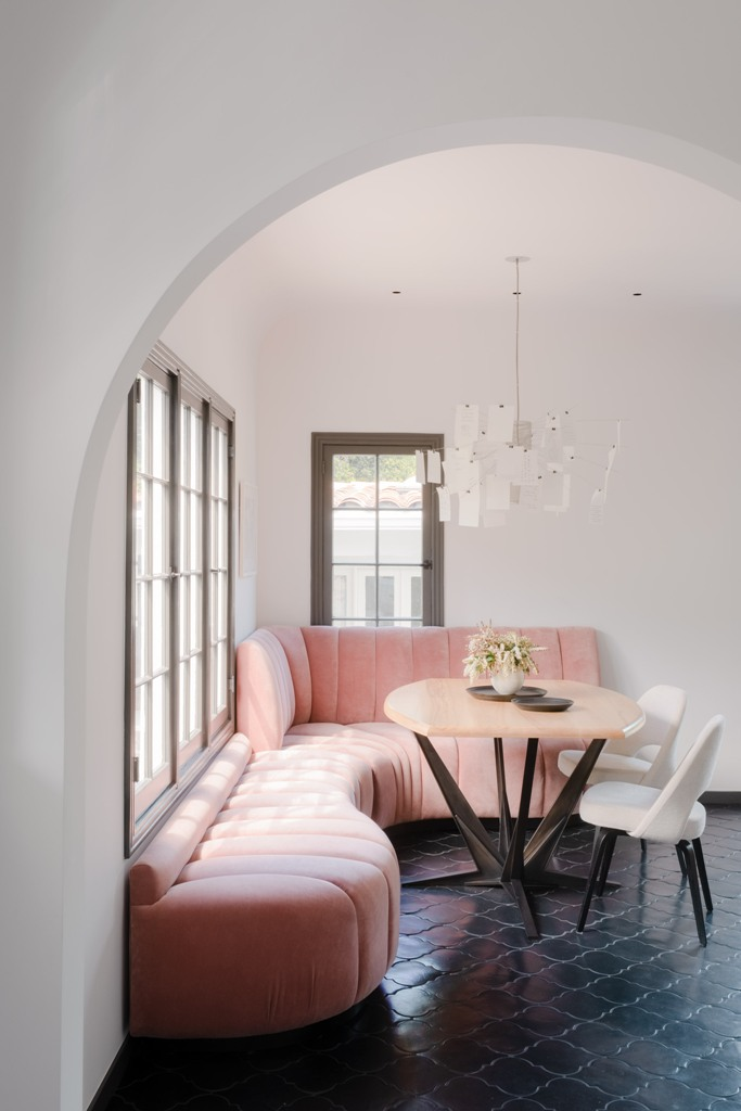 The breakfast zone shows off a pink upholstered corner sofa and some white chairs