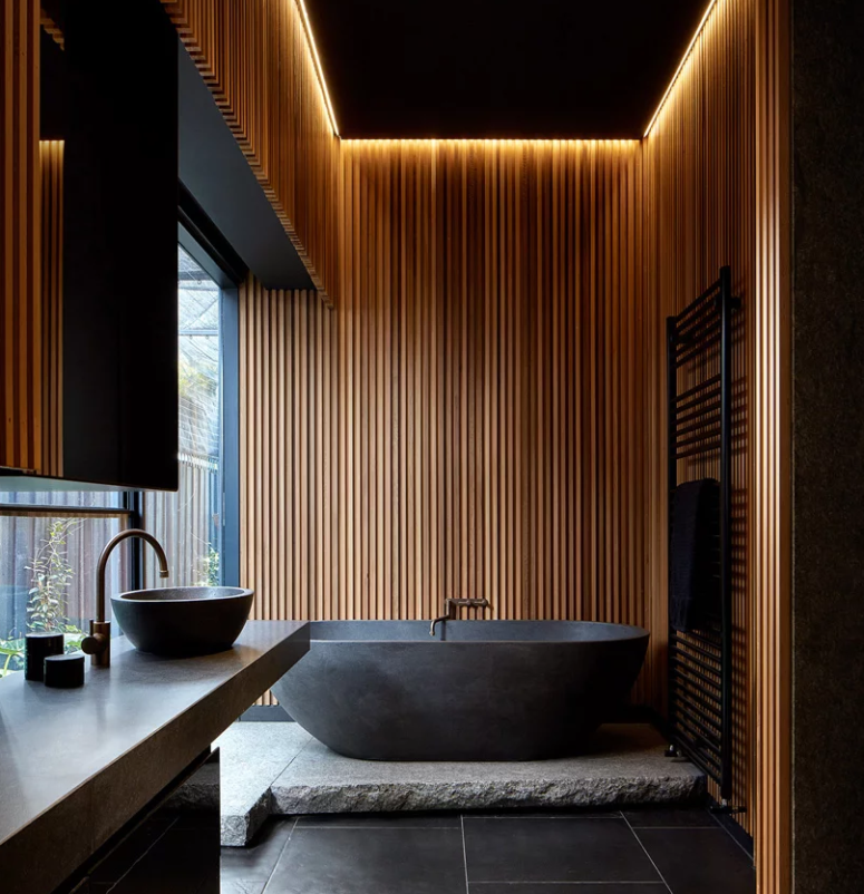 The wonderful moody bathroom is done with a stone tub on a platform, built-in lights over it, a stone vanity and some minimalist textures