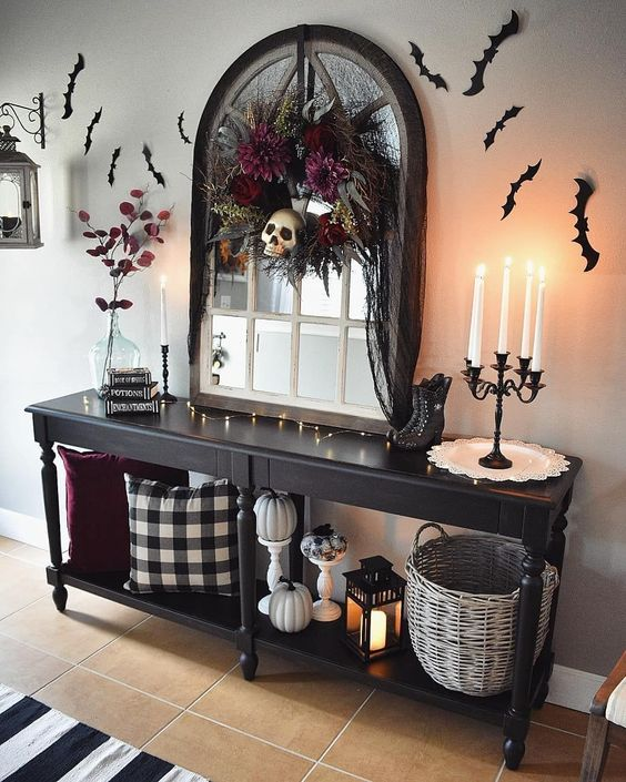 a Halloween entryway console with pumpkins, bats on the wall and a darkflorla wreath with a skull for a moody touch