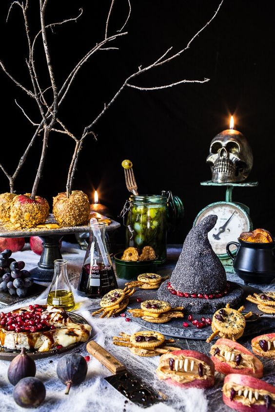 a buffet table styled with a sparky witch hat, some potion in bottles, a skull candleholder and some creepy treats