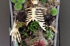 06 a coffin and skeleton centerpiece with succulents, moody blooms, greenery, hay and lights is a very creative idea
