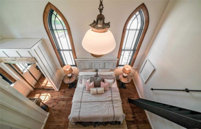 The bedorom is done with wooden floors, a comfy bed, a couple of nightstands and lamps