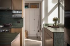 07 The kitchen is done with light-colored wood and green stone