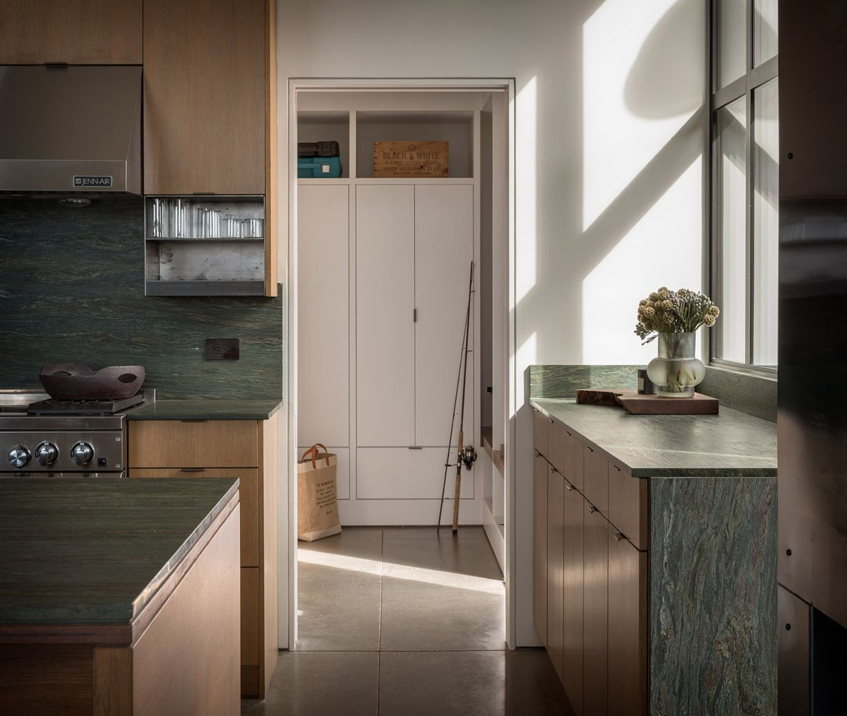 The kitchen is done with light colored wood and green stone