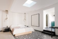 07 The master bedroom is done with a skylight, some pendant lamps, a tile floor and a statement artwork