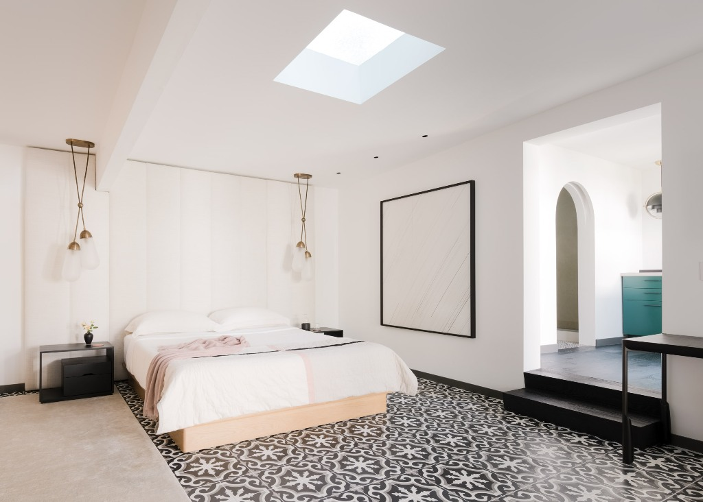 The master bedroom is done with a skylight, some pendant lamps, a tile floor and a statement artwork