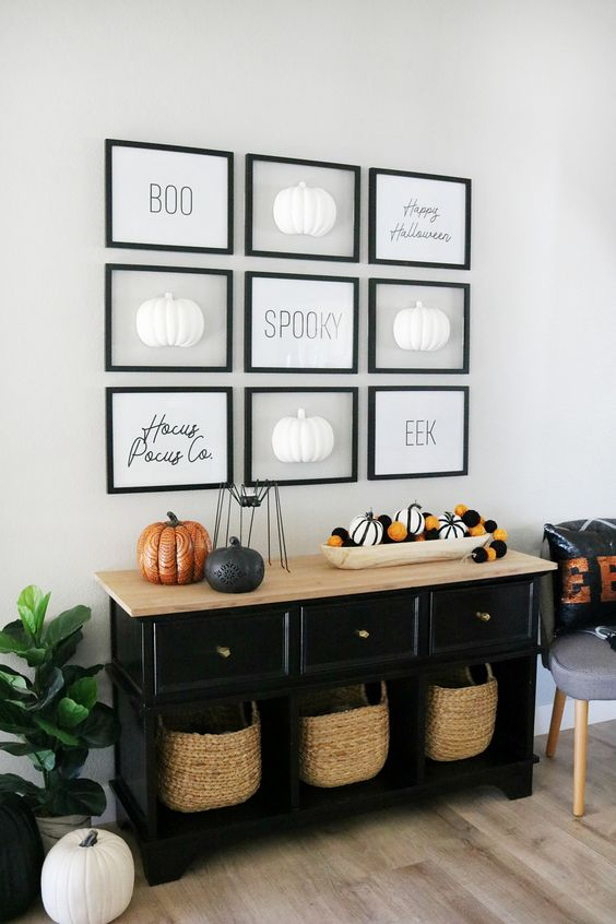 a Halloween entryway console with striped and black and orange pumpkins, a gallery wall with pumpkins and words