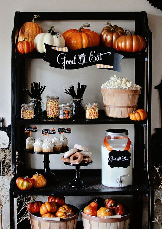 a dessert buffet with pumpkins in a basket, painted pumpkins on the upper shelf and some treats that match