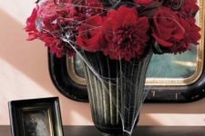 07 a moody vintage urn with sumptuous red blooms and some spiderweb is a traditional Halloween option that always works