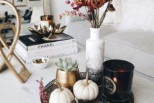07 a stylish fall arrangement of a tray with blakc and white embellished pumpkins, a black candleholder and dried blooms in an ombre vase