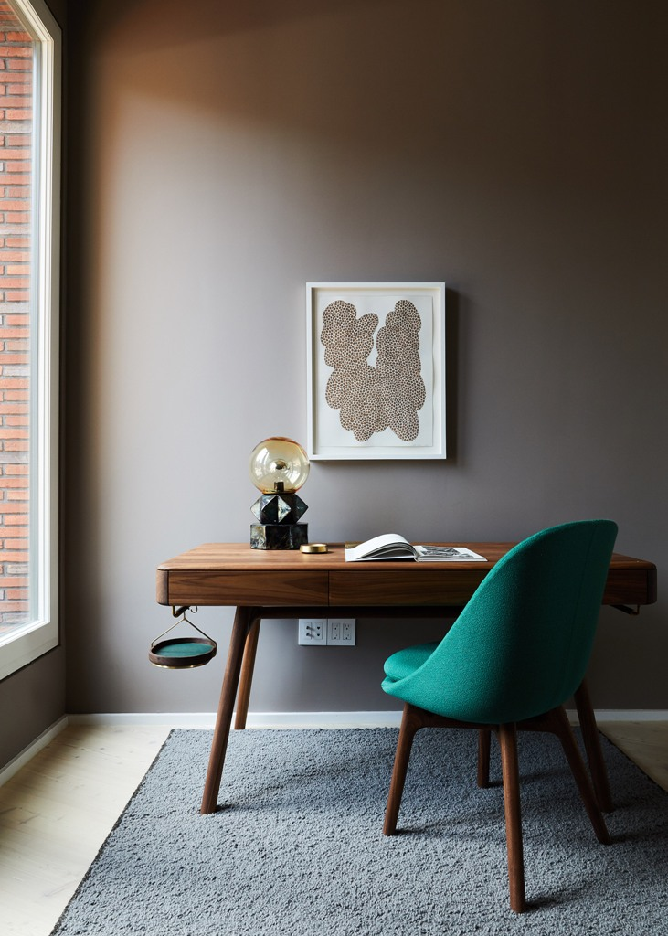 The cozy home office nook is furnished with a stylish sleek desk, an upholstered chair and a catchy table lamp