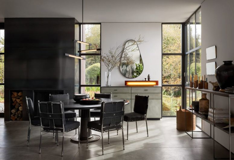 The dining space is done in black, with a unique mirror and a creative lamp