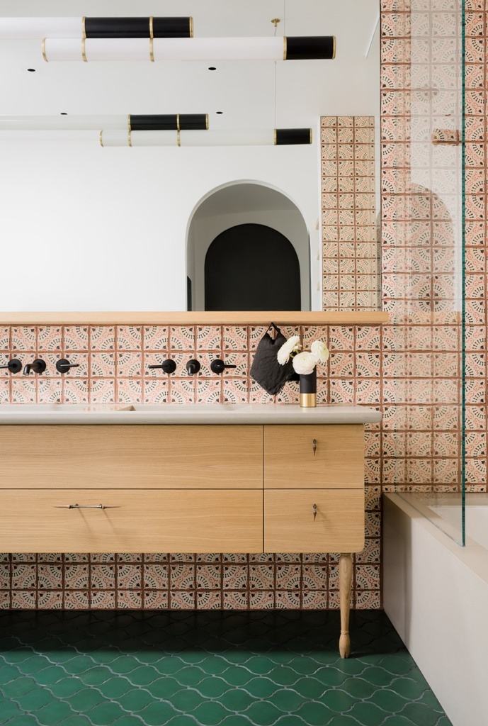 The master bathroom shows off unique tiles, a wooden vanity and a bright green floor